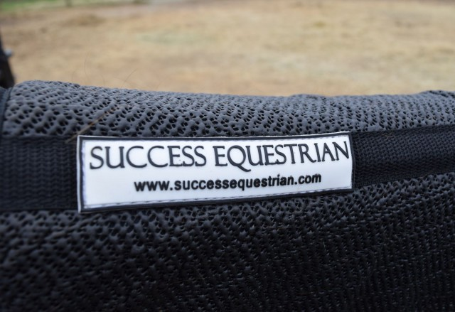 Success Equestrian Logo, on the spine of their Deluxe Jumper / All Purpose Non-Slip Pad, in black