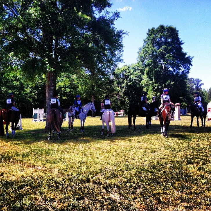 Training riders hang out beneath a shade tree during a hold on course to repair the chevron.