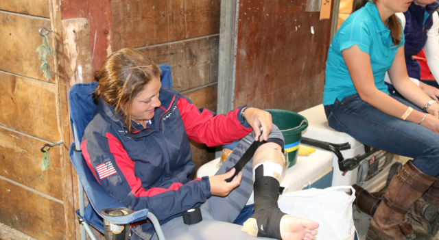Lynn Symansky bandaging up her leg in the barn on cross-country morning. Photo by Leslie Wylie.