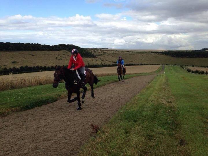 Jessica Phoenix & Peter Barry gallop up the hill. Photo via Phoenix Equestrian Team FB.