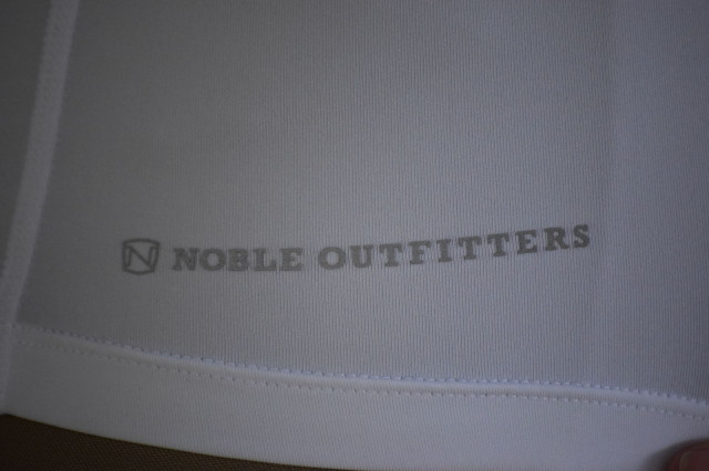 Noble Outfitters logo on near bottom hem on front of Amy Quarter Zip -  I find the detailing to be stylish, but I also like the concept of having  reflective areas on my clothing, since I often ride at dusk during the Fall - Photo by Lorraine Peachey