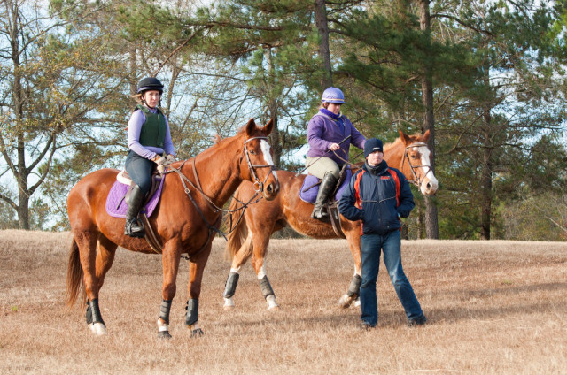 Kelly Vaughan Hanby riding Leon (left) and Holly Ratcliff riding Eddie with Francis Whittington during their cross-country lesson at Gibbes Farm. Photo by Leslie Threlkeld