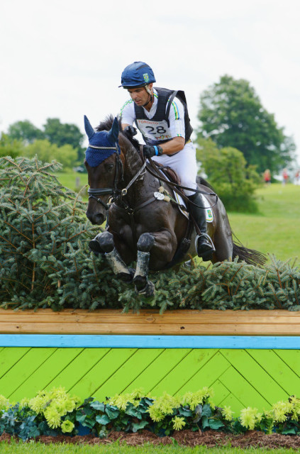 Ruy Fonseca takes a peak at his watch as he clears the last fence with Tom Bombadill Too. Photo by Jenni Autry.