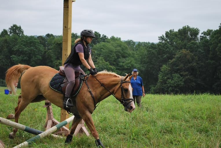 Phyllis instructs a rider through a picture frame jump. Photo by Erin McCormick.