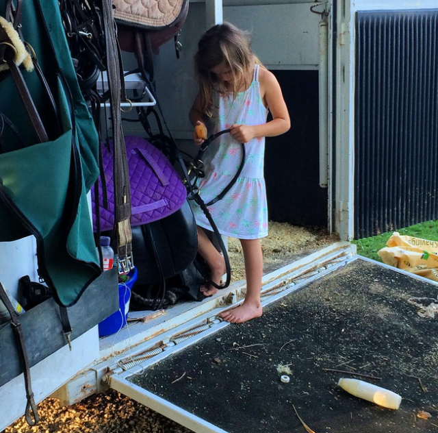 Claire helping her sister clean tack for an event. Photo courtesy of Anne Peters.