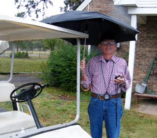 "Photo of Jack Ernst from The Hunks of Area V Calendar, submitted by Catherine Baker: ""Jack with his golf cart and timers and umbrella ready to volunteer at another event! Wonderful man that will be missed!"""