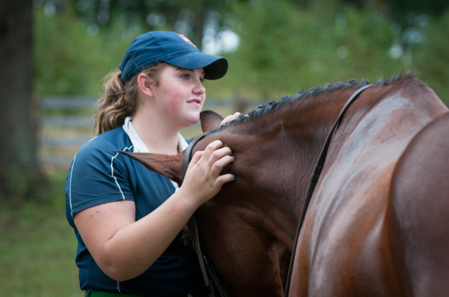 Groom Rachael Tuscher gives her charge, Carolina Fairfax, some well deserved snuggles after dressage on Saturday. Photo by Leslie Threlkeld.