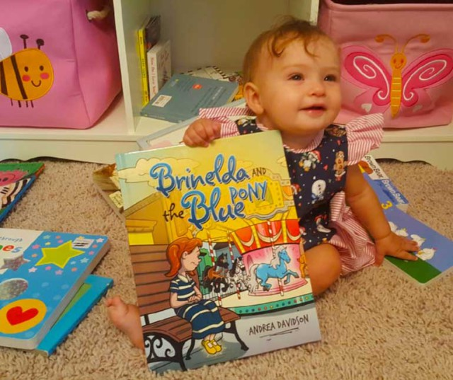 Aubrey Davidson proudly displays her mom's new book. Photo courtesy of Andrea Davidson.
