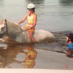 Ann Haller going above and beyond -- or in this case, neck deep in lake water -- for a new Pony Clubber. Photo courtesy of Shelby Allen.